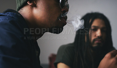 Buy stock photo Shot of two young men smoking a marijuana joint at home