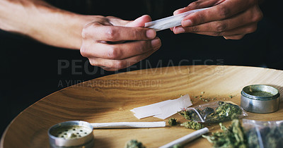 Buy stock photo Cropped shot of a man rolling a marijuana joint at home