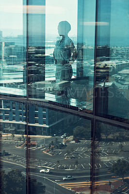 Buy stock photo Shot of a businesswoman standing inside a glass building with a reflection of the city in the background