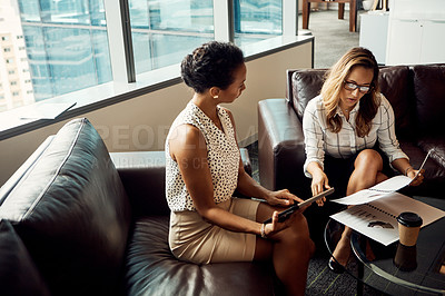 Buy stock photo High angle shot of two young businesswomen using a digital tablet while going over some paperwork in their office