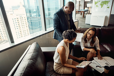 Buy stock photo High angle shot of a group of businesspeople using a digital tablet while going over some paperwork in their office