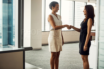 Buy stock photo Shot of two attractive young businesswomen shaking hands in an office