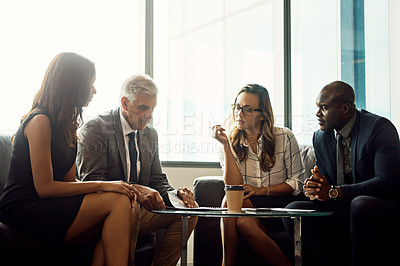 Buy stock photo Shot of a group of businesspeople going over paperwork during a meeting in an office