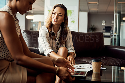 Buy stock photo Shot of two young businesswomen using a digital tablet while going over some paperwork in their office