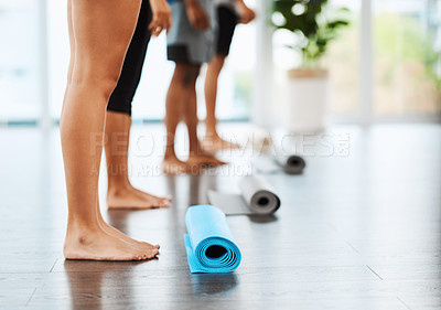 Buy stock photo Shot of an unrecognizable group of people standing with their yoga mats on the floor inside a studio