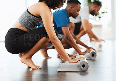 Buy stock photo Shot of group of young people rolling out their yoga mats inside a studio