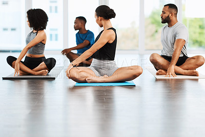 Buy stock photo Full length shot of a group of young people sitting down and practicing yoga together inside a studio
