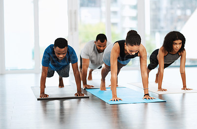 Buy stock photo Full length shot of a group of young people practicing yoga together inside a studio