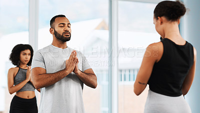 Buy stock photo Shot of a group of young people meditating and practicing yoga together inside a studio