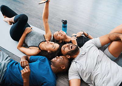 Buy stock photo Shot of a group of young people lying down and taking selfies with a cellphone together at a yoga class