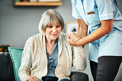 Buy stock photo Shot of a young nurse helping a senior woman get up from the sofa
