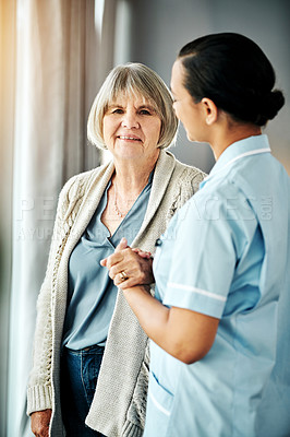Buy stock photo Shot of a young nurse looking out of a window together with an elderly woman at home