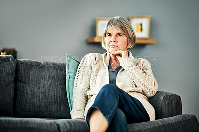 Buy stock photo Shot of a senior woman sitting on a sofa and looking thoughtful