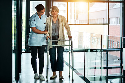 Buy stock photo Shot of a young nurse helping a senior woman with a walker