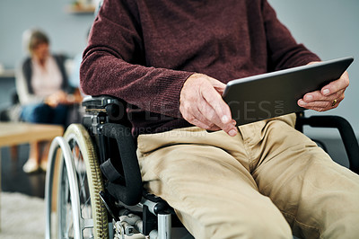 Buy stock photo Shot of a man using a digital tablet while sitting in a wheelchair