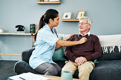Buy stock photo Shot of a senior man getting a checkup from a young nurse