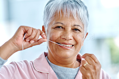 Buy stock photo Portrait of a cheerful elderly woman flossing her teeth while standing inside of the bathroom at home during the day