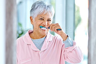 Buy stock photo Cropped shot of a carefree elderly woman brushing her teeth while looking into the mirror at home during the day