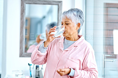Buy stock photo Cropped shot of a cheerful elderly woman taking medication with a glass of water inside of the bathroom at home during the day