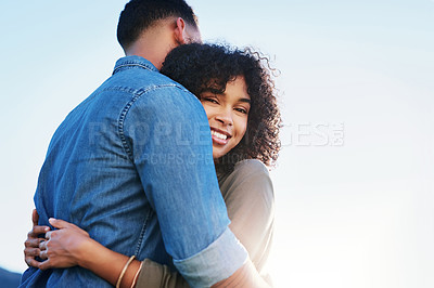 Buy stock photo Cropped portrait of an affectionate young couple hugging each other while on a date outside during the day