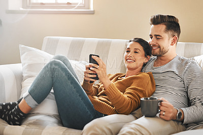 Buy stock photo Shot of a young couple using a cellphone while relaxing on the sofa at home
