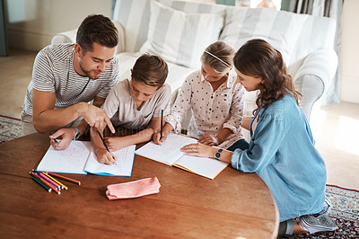 Buy stock photo Shot of a happy young family of four doing homework together
