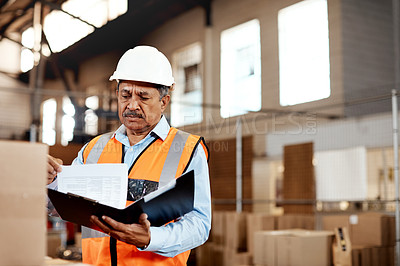 Buy stock photo Shot of a mature man doing inspections in a warehouse