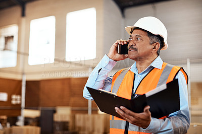 Buy stock photo Shot of a mature man using a smartphone while working in a warehouse