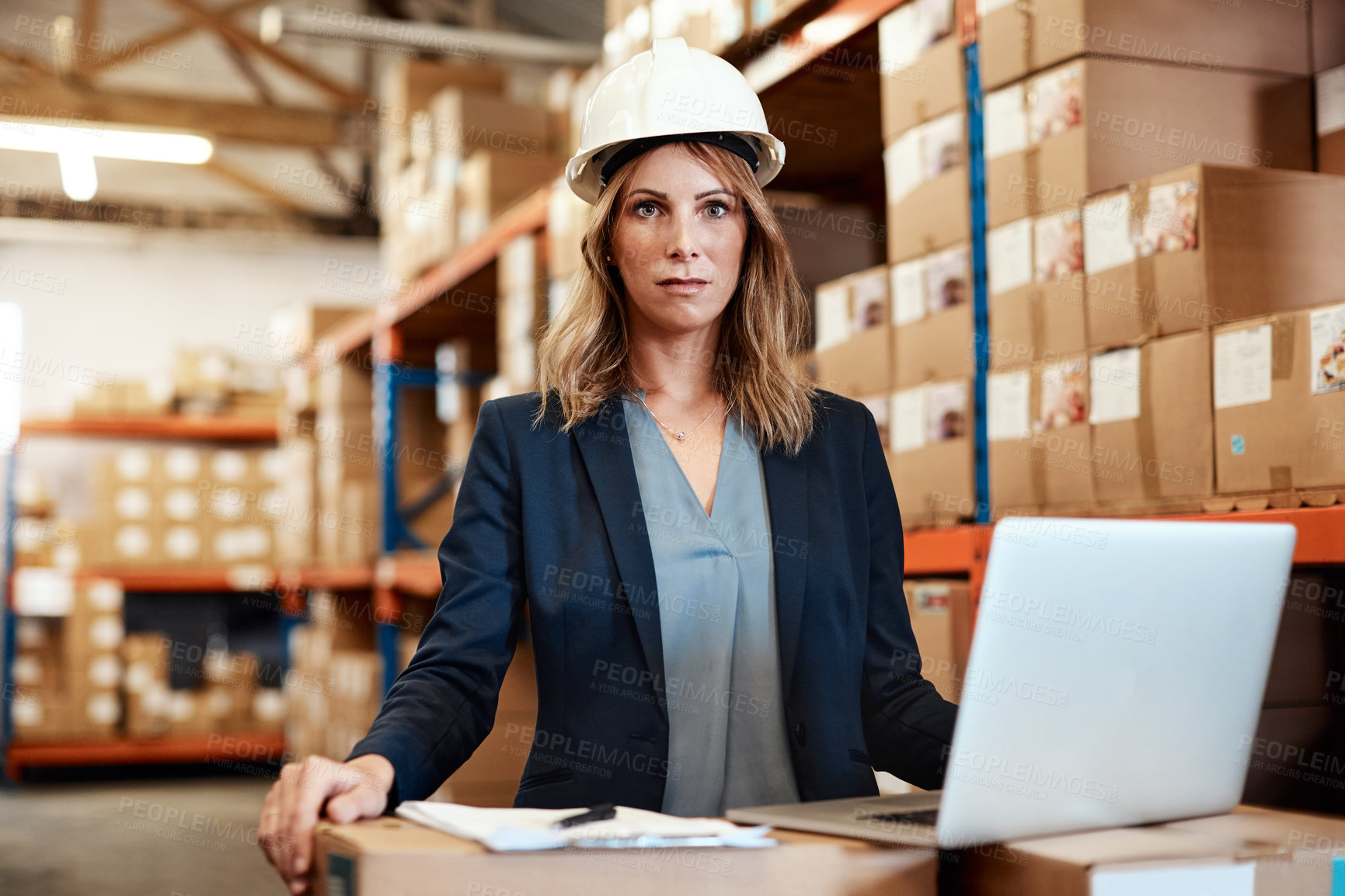 Buy stock photo Shot of a young woman using a laptop while working in a warehouse