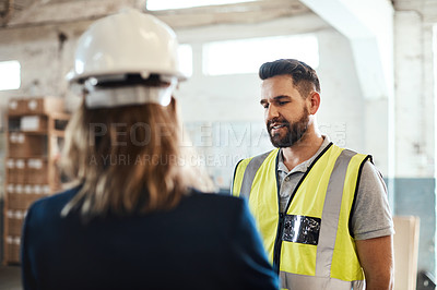 Buy stock photo Cropped shot of a handsome young male warehouse worker talking to his supervisor