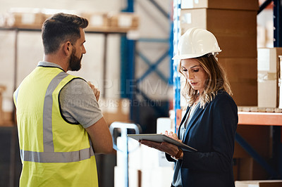 Buy stock photo Cropped shot of an attractive young female businesswoman talking to a male warehouse worker