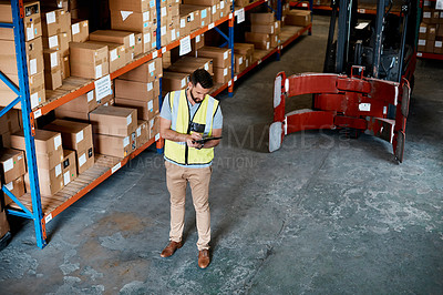 Buy stock photo High angle shot of a handsome young male warehouse worker checking stock