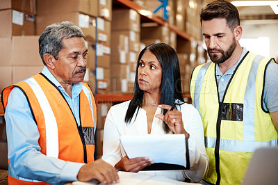 Buy stock photo Cropped shot of three warehouse workers checking on distribution logistics