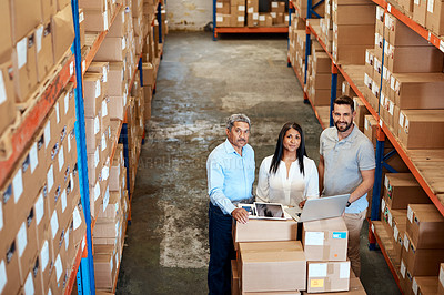 Buy stock photo High angle portrait of three warehouse workers checking on distribution logistics