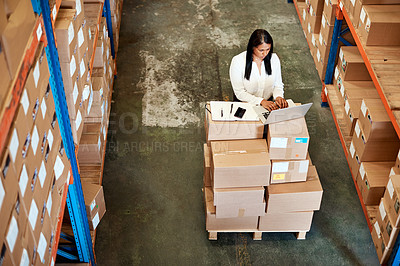 Buy stock photo High angle shot of an attractive mature female warehouse worker working on a laptop