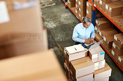 Buy stock photo High angle shot of a handsome mature male warehouse worker working on a laptop