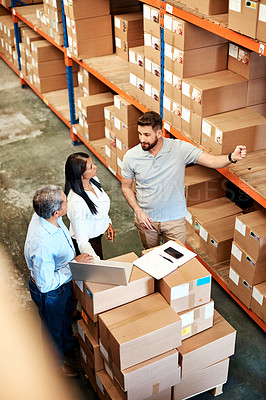 Buy stock photo High angle shot of three warehouse workers checking on distribution logistics