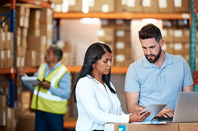 Buy stock photo Shot of a man and a woman using a digital tablet while working together in a warehouse