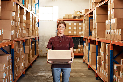 Buy stock photo Portrait of a young woman holding a box while working in a warehouse
