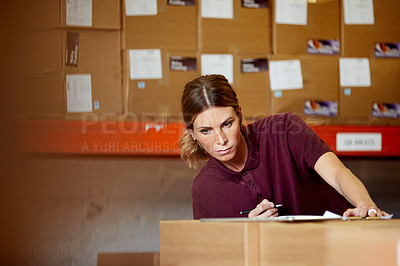 Buy stock photo Shot of a young woman working in a warehouse