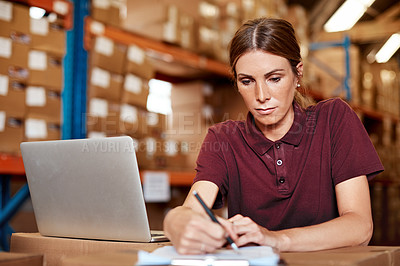Buy stock photo Shot of a young woman writing notes while using a laptop in a warehouse