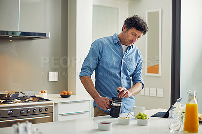 Buy stock photo Shot of a mature couple having coffee in the kitchen at home