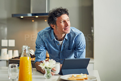 Buy stock photo Shot of a mature man looking thoughtful while having breakfast and using a digital tablet at home