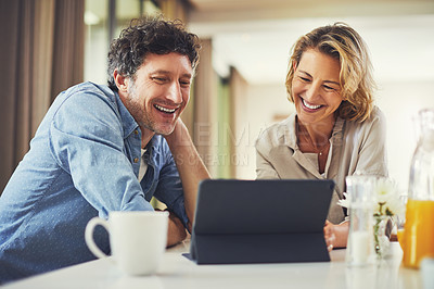 Buy stock photo Shot of a mature couple using a digital tablet while having breakfast at home