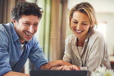 Buy stock photo Shot of a mature couple using a digital tablet at home