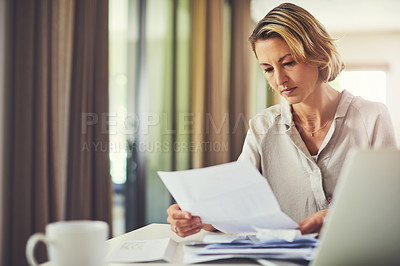 Buy stock photo Shot of a mature woman going over her finances at home