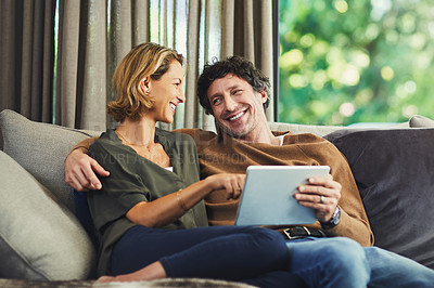 Buy stock photo Shot of a mature couple using a digital tablet on the sofa at home