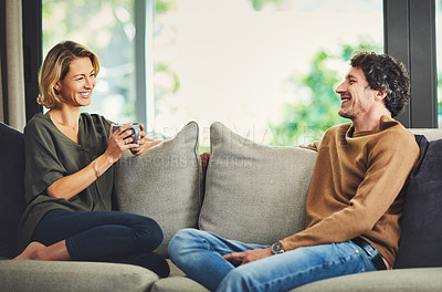 Buy stock photo Shot of a mature couple chatting and having coffee while relaxing on the sofa at home