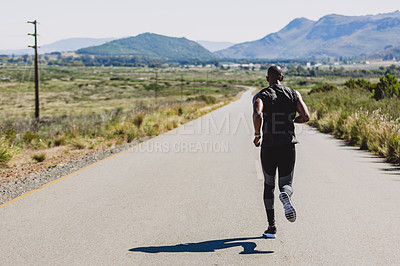 Buy stock photo Shot of a sporty young man out running on a country road