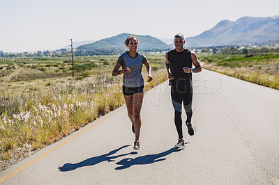 Buy stock photo Shot of two sporty young people running out on a country road